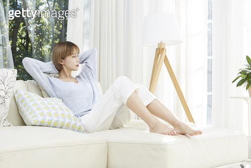 소파에 앉아서 휴식하는 젊은여자 - gettyimageskorea