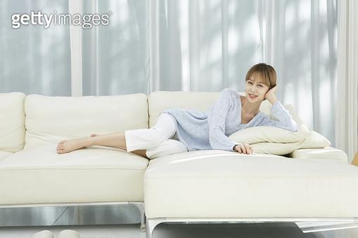 소파에 누워서 휴식하는 젊은여자 - gettyimageskorea