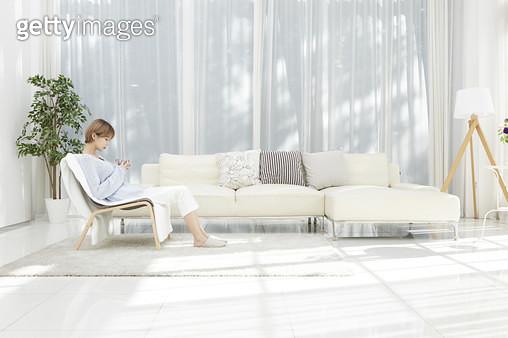 찻잔을 들고 거실 소파에 앉아 휴식하는 젊은여자 - gettyimageskorea