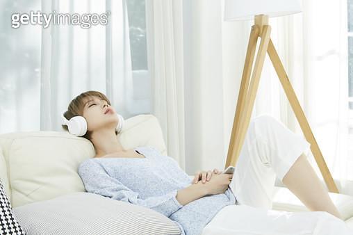 소파에 편하게 기대앉아 헤드폰을 쓰고 휴식하는 젊은여자 - gettyimageskorea