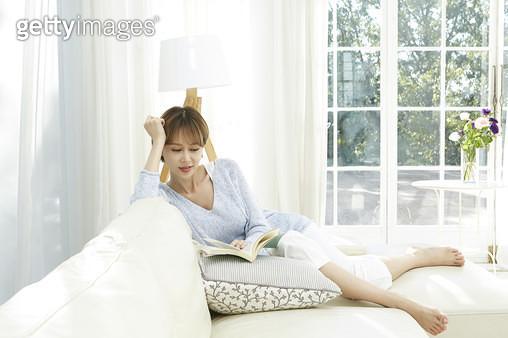 소파에 편하게 기대앉아 책을 읽는 젊은여자 - gettyimageskorea