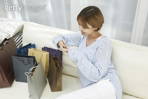 많은 쇼핑백을 보며 휴대폰으로 사진촬영하는 젊은여자 - gettyimageskorea