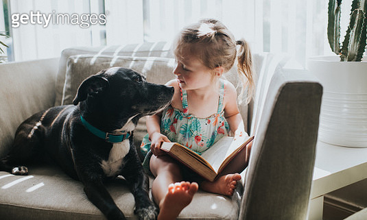 Cute little girl reads a book with her dog. - gettyimageskorea