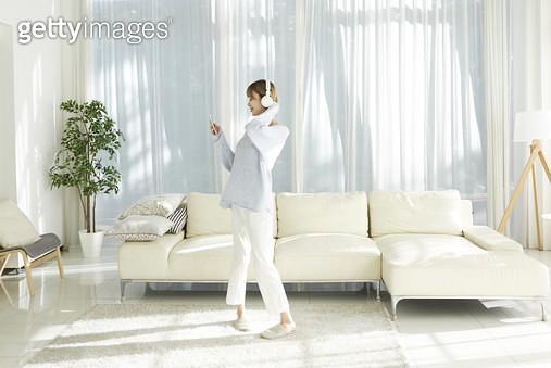 거실에 서서 헤드폰을 쓰고 춤을추는 젊은여자 - gettyimageskorea