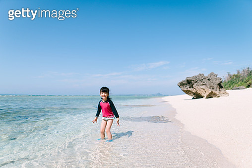 Preschool girl playing in shallow tropical water with white sand beach, Japan - gettyimageskorea