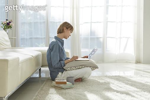 거실 바닥에 앉아 노트북을 하는 젊은여자 - gettyimageskorea