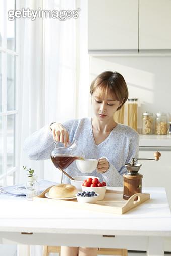 식탁에 앉아 커피잔에 커피를 따르는 젊은여자 - gettyimageskorea
