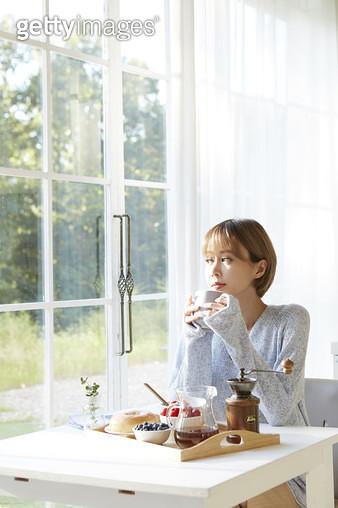 식탁에 앉아 커피를 마시며 창밖을 바라보는 젊은여자 - gettyimageskorea