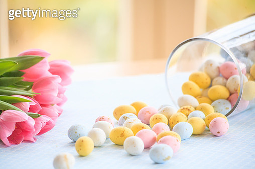 Graphical composition of eggs fallen out of a glass jar and tulips bunch on a table in a nice and cosy interior. Close-up and warm side light. Blurred background and focus on the foreground. - gettyimageskorea