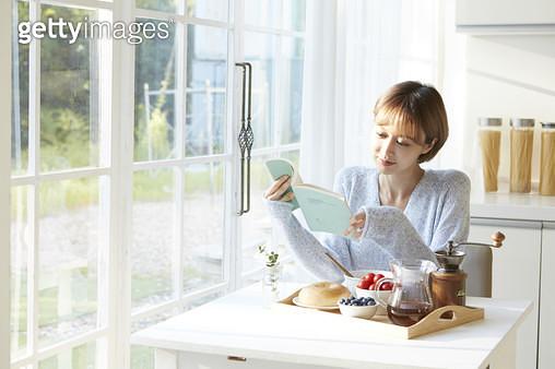 음식이 차려진 식탁에 앉아 책을 읽는 젊은여자 - gettyimageskorea