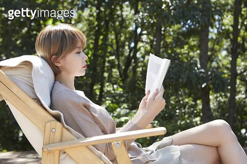 야외 테라스에서 책을 읽으며 쉬는 젊은여자 - gettyimageskorea