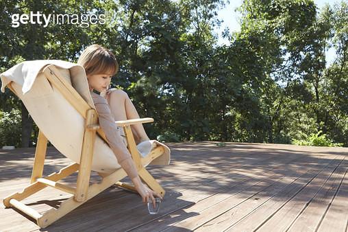 야외 테라스의 의자에 앉아 물컵을 잡는 젊은여자 - gettyimageskorea