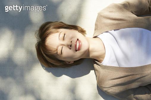 햇빛이 눈이부셔서 눈을 감은 누워있는 젊은여자 - gettyimageskorea