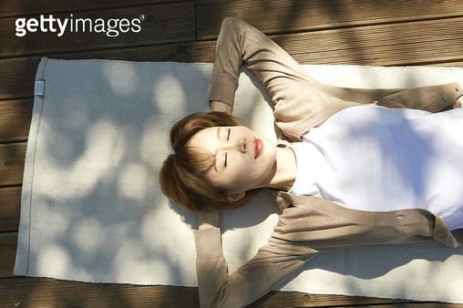 햇빛 아래 누워 눈감감고 쉬고 있는 젊은여자 - gettyimageskorea