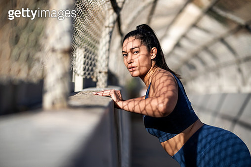 Healthy woman doing push-ups over a concrete wall. Plus size female in sportswear exercising outdoors. - gettyimageskorea