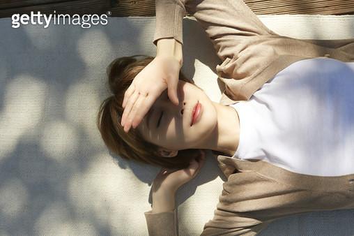 햇빛을 가리며 누워서 쉬고있는 젊은여자 - gettyimageskorea
