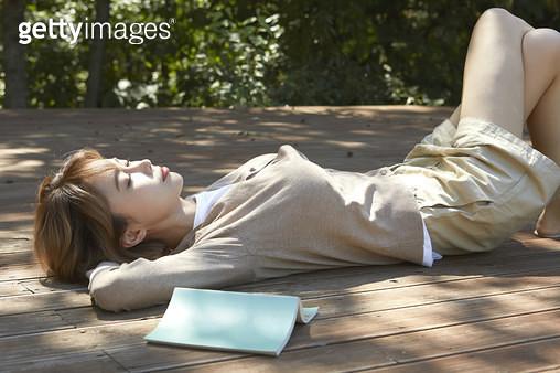 나무 데크에 누워 편안하게 쉬고있는 젊은여자 - gettyimageskorea