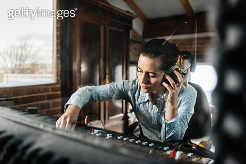 A female sound engineer in a recording studio working on a track behind a glass window - gettyimageskorea