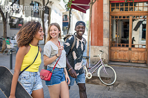 Smiling friends talking while walking in city - gettyimageskorea