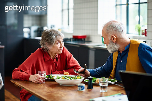 Retired man and woman sitting at dining table in modern kitchen, eating salad and talking, woman looking at man and listening with surprised expression - gettyimageskorea