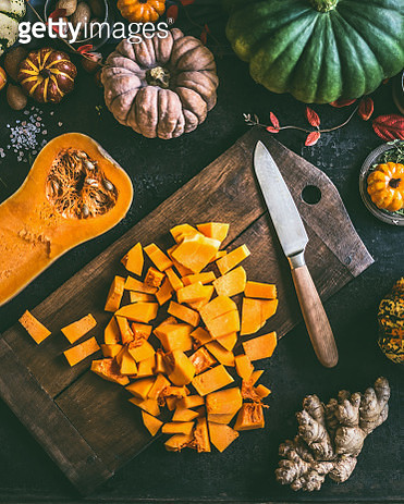 Diced ​​Pumpkin on cutting board with knife - gettyimageskorea