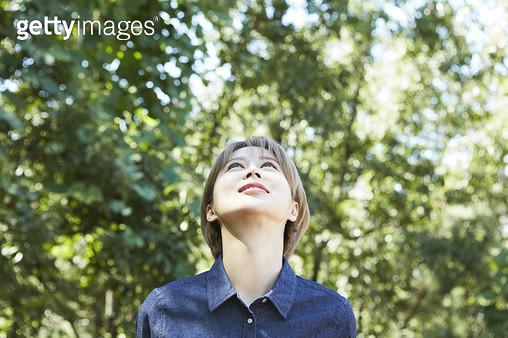 위를 올려다보는 젊은여자의 앞모습 - gettyimageskorea