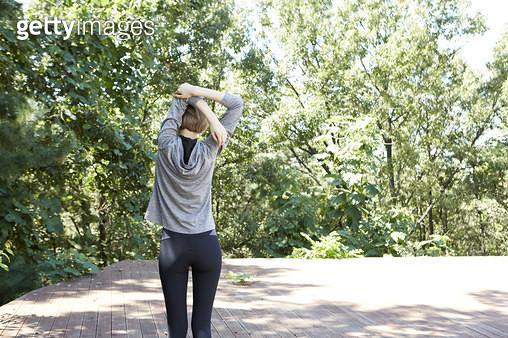 운동복을 입고 서서 스트레칭 하는 젊은여자의 뒷모습 - gettyimageskorea
