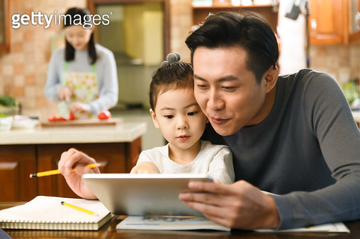 Dad and daughter watch tablets - gettyimageskorea
