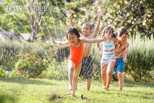 Children running through water sprinkler - gettyimageskorea