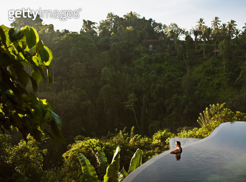 Female guest in two-tier infinity pool at Ubud Hanging Gardens, Bali, Indonesia. The infinity pool faces the lush Ayung River valley. - gettyimageskorea