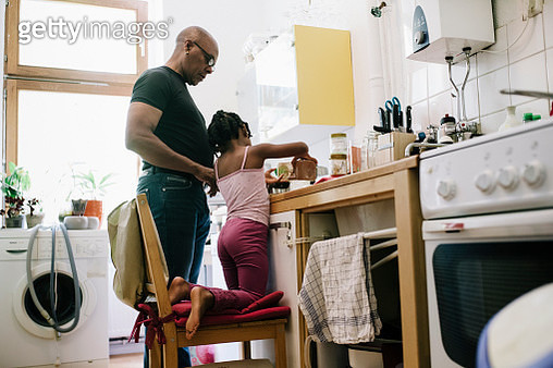 A dad letting his young daughter, who is kneeling on a chair to reach the counter, help out in the kitchen and make lunch. - gettyimageskorea