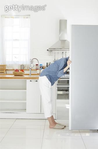 냉장고 문을 열고 안을 들여다보는 젊은여자의 옆모습 - gettyimageskorea