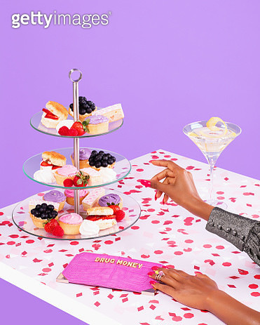 A female hand is reaching for Afternoon Tea with a Martini. - gettyimageskorea