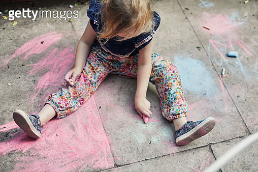 Toddler girl drawing outside on the floor with chalk - gettyimageskorea