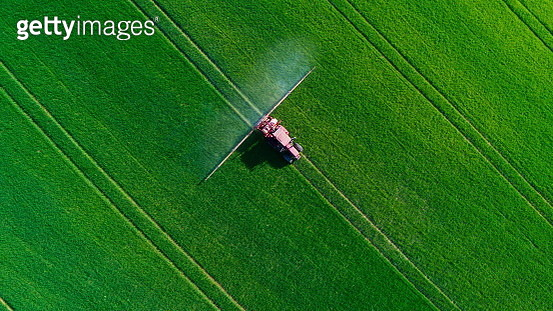 Tractor spraying field - gettyimageskorea