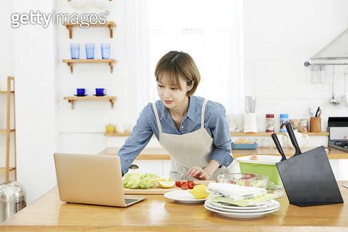 주방 조리대에서 음식을 요리하면서 노트북으로 레시피를 보고 있는 젊은여자 - gettyimageskorea