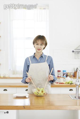 주방 조리대에서 샐러드를 만들고있는 젊은여자 - gettyimageskorea