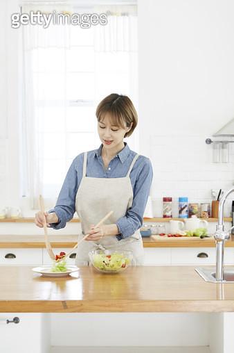 주방 조리대에서 샐러드를 접시에 담고있는 젊은여자 - gettyimageskorea