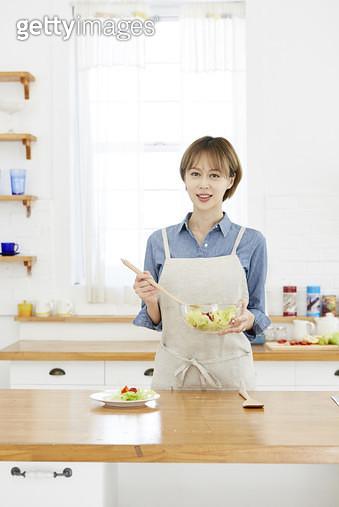 주방 조리대에서 샐러드볼을 들고 서 있는 젊은여자 - gettyimageskorea