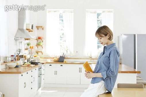 주방을 배경으로 옆으로 서서 책을 들고있는 젊은여자 - gettyimageskorea