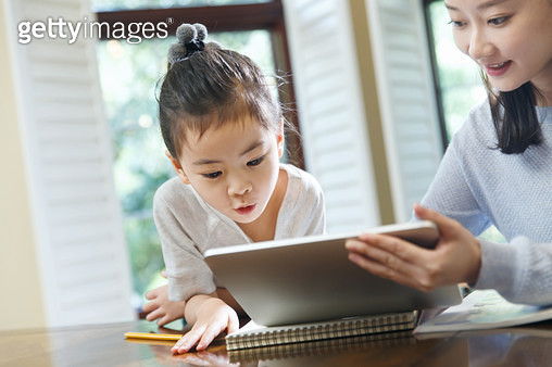 Mother and daughter watch tablets - gettyimageskorea