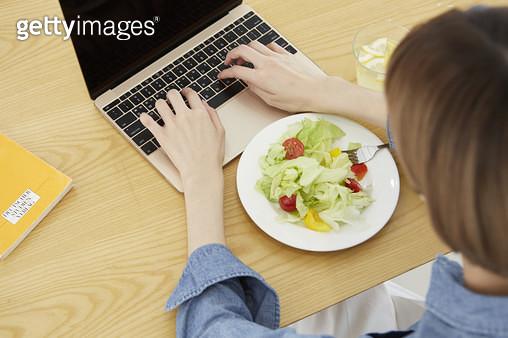샐러드와 노트북 타이핑을 하는 젊은여자 - gettyimageskorea