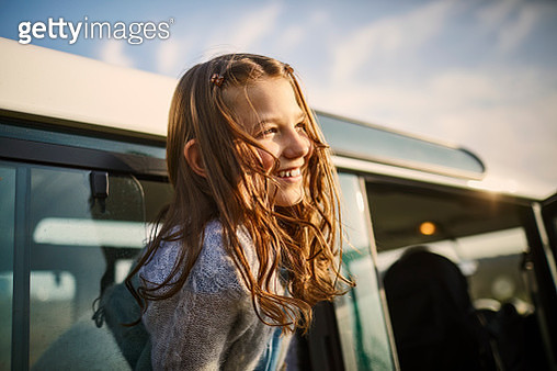 Happy girl looking out of window of an off-road vehicle - gettyimageskorea