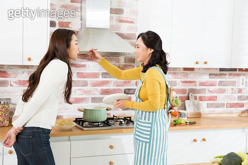 요리하는 엄마와 맛을 보는 딸 - gettyimageskorea