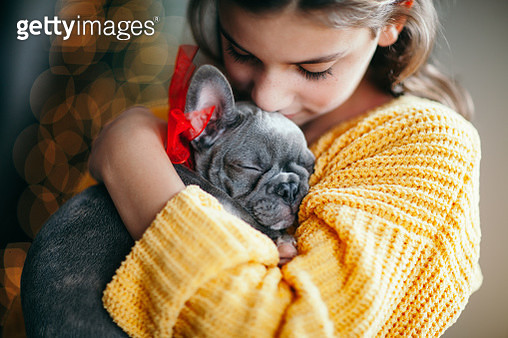 girl cuddling puppy she received as Christmas gift - gettyimageskorea