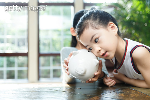 The sisters put the money in the piggy bank - gettyimageskorea
