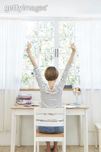 책상에 앉아 기지개를 펴는 동작으로 스트레칭하는 젊은여자의 뒷모습 - gettyimageskorea