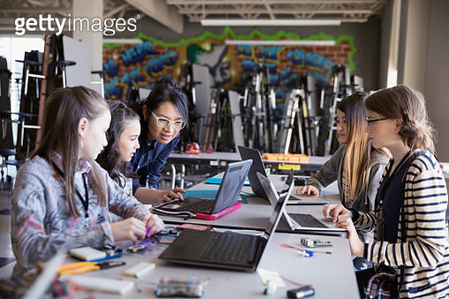 Female teacher helping pre-adolescent girls programming at laptops in classroom - gettyimageskorea