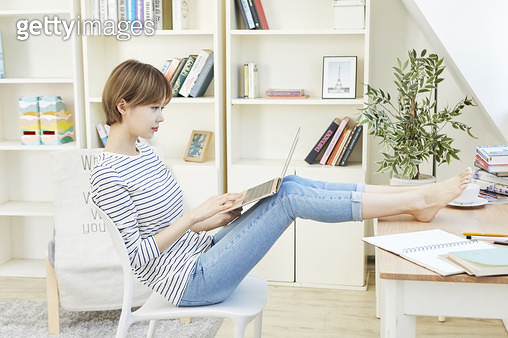 다리를 책상에 올리고 의자에 앉아 노트북을 하는 젊은여자 - gettyimageskorea
