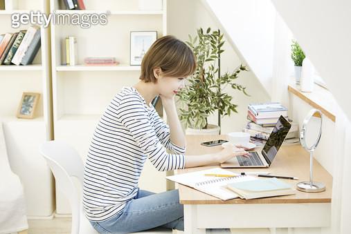 의자에 앉아 책상에 턱을 괴고 노트북을 하는 젊은여자 - gettyimageskorea